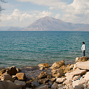 An Afghan man looks out to sea from outskirts of the Greek city of Patras, close to a place dubbed 'the jungle' by locals, where illegal migrants sleep amid trees close to the beach.