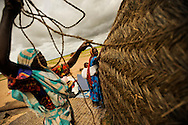 Women build a shelter of sticks and swaths of cloth in Abougoudam, a village of Chadian Arab nomads. Abougoudam is in a remote area of Eastern Chad a several hours drive from Abeche.