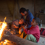 Bedouin man playes with kids in a bedouin tent (sheeg).  Photo by Oren Nahshon