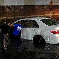 Good Samaritans help push a car out of flood waters on Washington Street in Worcester, Massachusetts on October 21, 2016.  Flash flooding in the area left many motorists stranded and closed down parts of route I-290.  Photo Copyright Matthew Healey<br /> <br /> (FREELANCE SUBMISSION)
