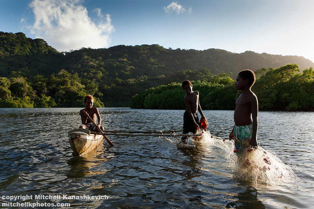 Young, teenage boys fishing with a net in a lagoon in South West Bay, Malekula
