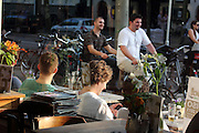 People cycle past a bar in Amsterdam - people cycle everywhere
