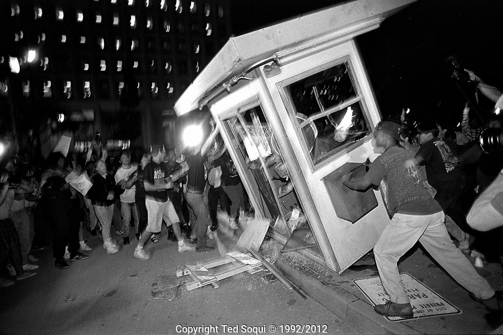 A kiosk near LAPD HQ, Parker Center, gets overturned and set ablaze by rioters. 4/29/1992