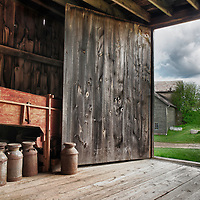 Antique milk cans in a barn, overlooking other buildings and grassy fields at Hancock Shaker Village.