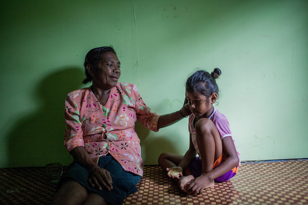 Mama Yuli comforts her granddaughter Anace (8). They are very close. In 2004 Mama Yuli contracted the HIV virus from her husband who later died from AIDS. At her worst point, Mama Yuli was just skin and bones weighing only 22 kilograms (48 pounds). With ARV she is now healthy to work and support her family.<br /> <br /> If taken properly and regularly, ARV has been proven to prolong the survival rate of people living with HIV/AIDS and enables them to live a productive life. The Indonesian government started providing ARV therapies in 2003. In that year only 7 packages of ARV were purchased for all of Papua. Each package cost approximately $5000. Today in Indonesia this vital medication can be obtained at no cost only in Papua but only 12% of those with HIV/AIDS are undergoing ARV therapy.<br /> <br /> Despite these advances, ARV is mostly available only in cities. Collaboration between health facilities in urban centers and staffs in rural areas to make ARV more accessible for patients living in the countryside is still lacking as well as the endorsement of ARV as a legitimate medicine for HIV/AIDS. Sometimes health staff and even educational materials still provide misleading information and perception such as &quot;there is no medicine for HIV/AIDS.&quot;<br /> <br /> As a general practice health personnel often evaluate patients for their adherence in taking their medication and keeping up with appointments before allowing them to undergo ARV therapy. Indigenous Papuans tend to fall short of this assessment and fail to return for their check-up because many of them live too far from the health centers.  At times, they do not fully understand the benefits of ARV medication and the importance of taking them properly due to poor counseling from the health staff.  Also, many of them are unable to keep their appointments or take medication regularly because they still keep their status a secret from their immediate family members or spouse.