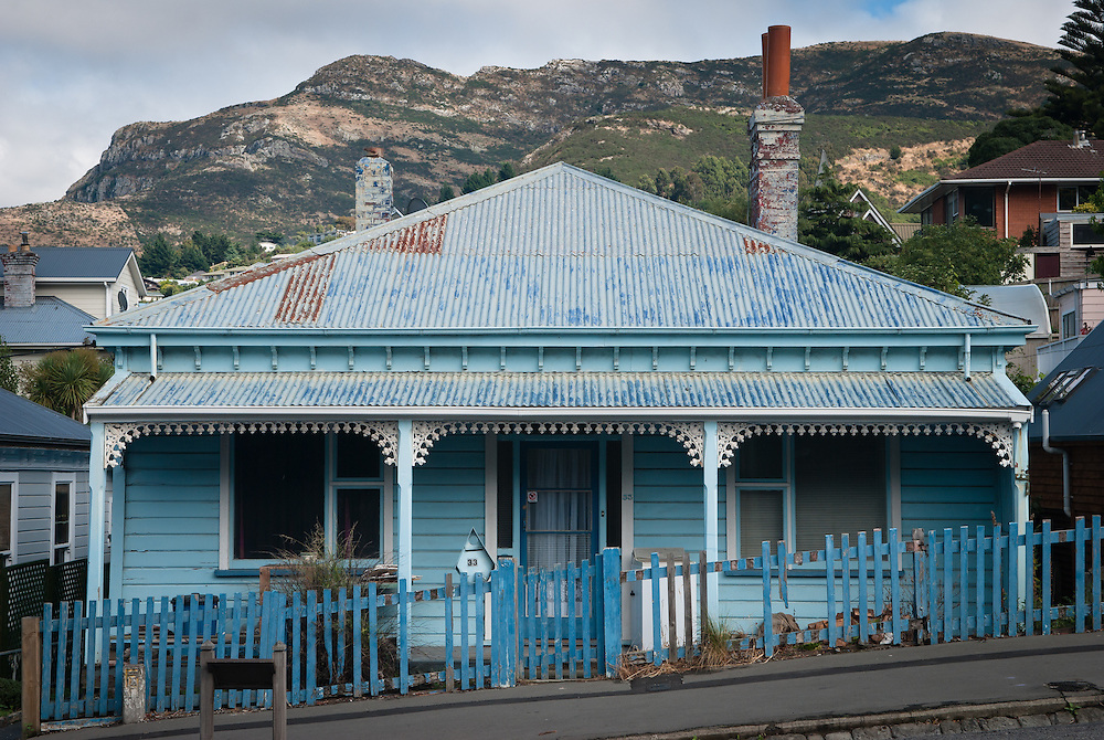 Typical mid-19th century colonial-style cottage, with tin roof, veranda and cast-iron filligree, Lyttleton NZ