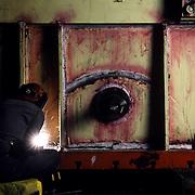 Welder repairing hopper in auto manufacturing plant, Metalsa, S.A. Monterrey, Mexico.