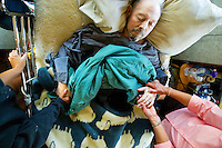 JEROME A. POLLOS/Press..June 12, 2007 -- Joni Connelly, a nurse with Hospice of North Idaho, and Nancy Warner holds the hands of her husband, Dick Warner, as he falls asleep following an increased dosage of morophine to ease his pain.