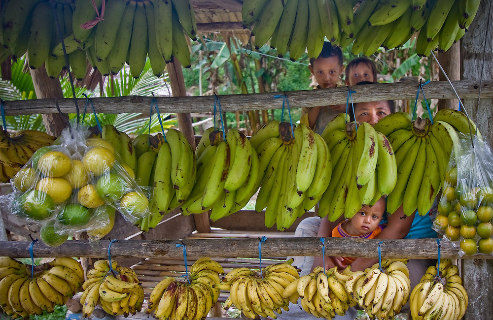 A family peers from behind rows of bananas and limes at a roadside stall in Central Sulawesi