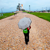 Onlookers cover under umbrellas as Space shuttle Atlantis STS-135 sits on the launch pad 39A in the rain at the Kennedy Space Center in Cape Canaveral, Florida July 7, 2011. REUTERS/Chip Litherland   (UNITED STATES)