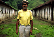 Worker from Roca Bombaim (Bombay Farm) poses in front of the buildings where used to live the slaves brought to work in this farm. Until the beggining of 20th century a different kind of slavery was put in practise by farm owners that, dispite the end of slavery, took advantage of the fact that free slaves didn't had the money to pay their trip back to Angola or Cape Verde.