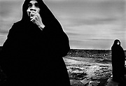 BAM, Iran - Women wait near the massgraves to bless the women and girls who died the in massive earthquake that devastated BAM.  According to the Muslim faith, females are supposed to be blessed by a female relative or another woman before they are buried.
