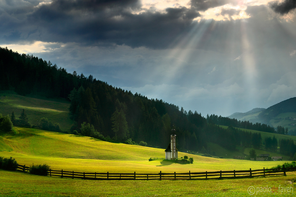 Some suggestive sun rays hit the small chappel of Saint Johann and the surrounding grass fields, as the sky starts to clearing-off after a mighty summer thunderstorm. Taken at the top of Val di Funes on an evening at the end of June, this is stitched from five vertical frames.