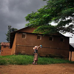A child with albinism takes her plate to the dining hall as a storm comes in at the Kabanga  Protectorate School for the Disabled in Tanzania.