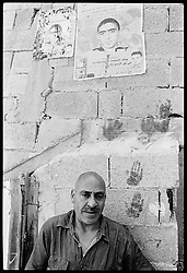 Aamer Abdullah was 16 when he detonated a bomb, killing himself and three others in Tel Aviv on Nov 1, 2004. Here Aamer's father stands beneath a poster of his son outside their old home, which was mostly destroyed by Israeli forces after the bombing.