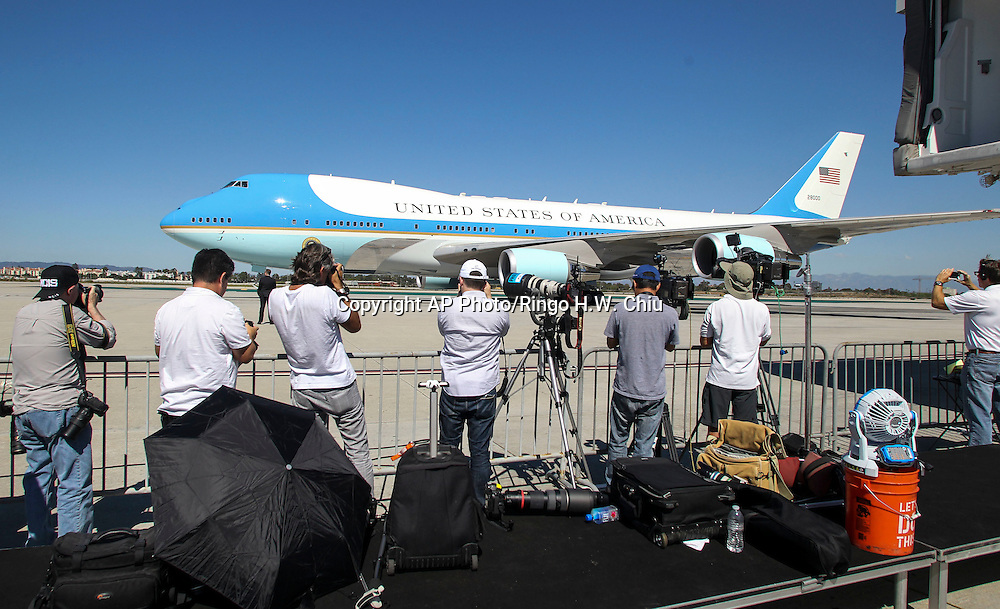 Members of the local news media cover Air Force One, with President Barack Obama aboard, taxis at Los Angeles International Airport in Los Angeles on Saturday, Oct. 10, 2015. (AP Photo/Ringo H.W. Chiu)