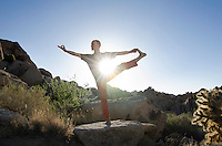 Man in the yoga pose Utthita Hasta Padangustasana (Extended Hand-To-Big-Toe Pose) while balanced in a desert landscape with the sun bursting through his core.