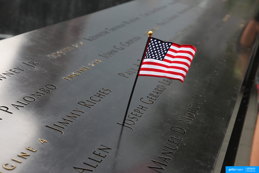 A flag amongst the names of the those who died at the National September 11 Memorial in Downtown Manhattan, New York City, USA. 16th September 2014. Photo Tim Clayton