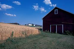 farm barn near suburban expansion project of town house apartments.