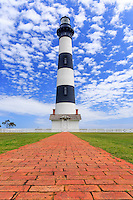 Bodie Island Lighthouse red brick walkway leading up to the lighthouse and a blue sky with puffy white clouds.