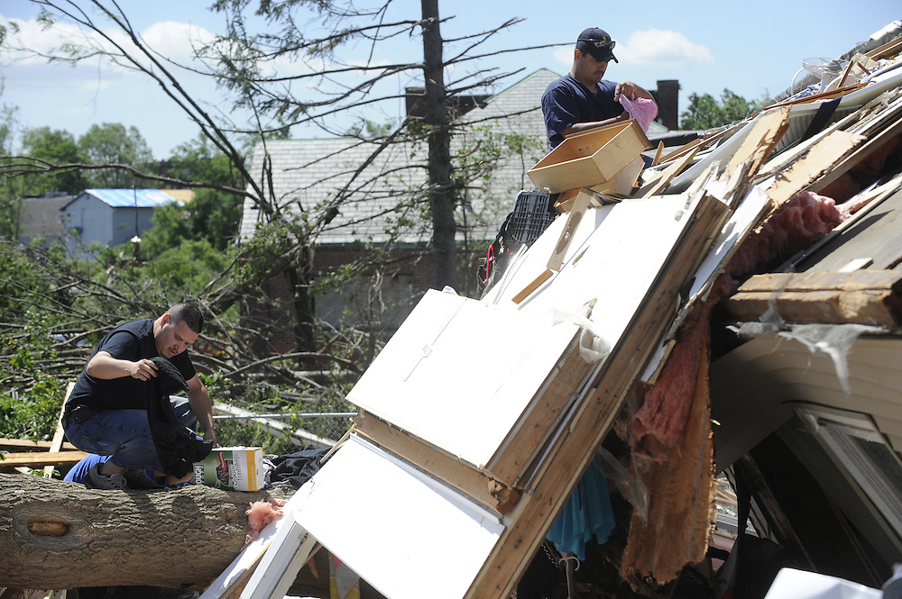 People sort through clothes on a rooftop a day after a tornado in Springfield, Mass., Thursday, June 2, 2011.  (AP Photo/Jessica Hill)