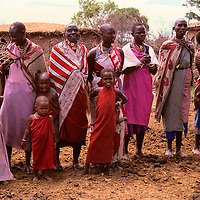 Africa, Kenya, Maasai Mara. Maasai mothers and children greet visitors to their boma at Olanana in the Maasai Mara.
