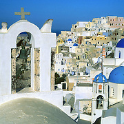 "Bell towers and blue-domed Greek Orthodox Churches grace the village of Oia on Santorini Island, an ancient volcanic caldera rim in the Aegean Sea, in Greece, Europe. After major destruction in a 1956 earthquate, Oia town was rebuilt as a multi level maze of fascinating whitewashed architecture. Published in PC Photo Magazine June 2002. Published in ""Light Travel: Photography on the Go"" book by Tom Dempsey 2009, 2010."