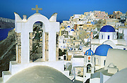 """Bell towers and blue-domed Greek Orthodox Churches grace the village of Oia on Santorini Island, an ancient volcanic caldera rim in the Aegean Sea, in Greece, Europe. After major destruction in a 1956 earthquate, Oia town was rebuilt as a multi level maze of fascinating whitewashed architecture. Published in PC Photo Magazine June 2002. Published in """"Light Travel: Photography on the Go"""" book by Tom Dempsey 2009, 2010."""