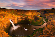 Palouse Falls plunges 180 feet (55 meters) into a giant natural amphitheater surrounded by towering columnar basalt walls near Washtucna, Washington. Palouse Falls was formed at the end of the last ice age when a mammoth ice dam in Montana regularly collapsed, releasing a torrent of water that carved this winding gorge.