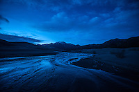 Medano Creek flows across the sands at dusk in Great Sand Dunes National Park and Preserve, Colorado.