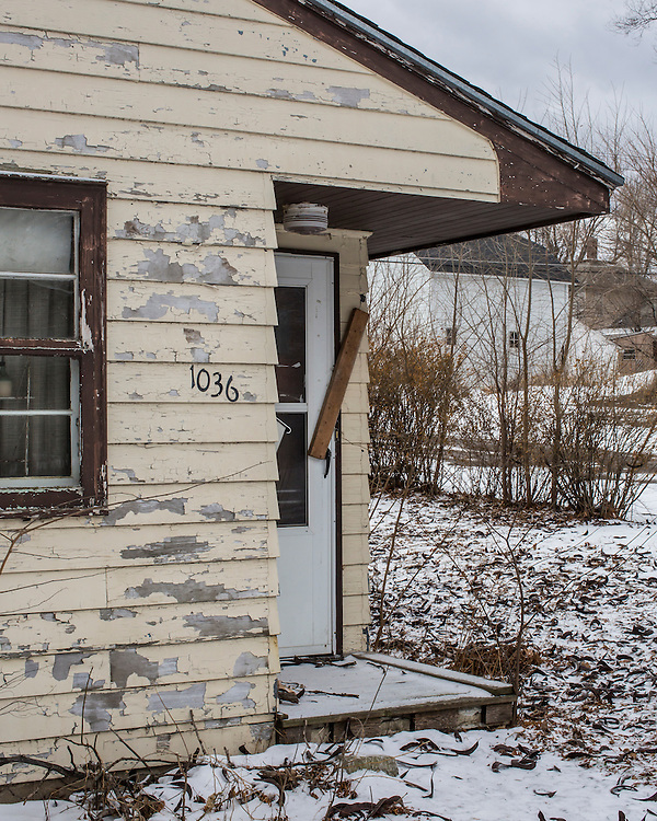 The door to an abandoned house is sealed with a board on Thursday, January 16, 2014, in Webster City, IA.