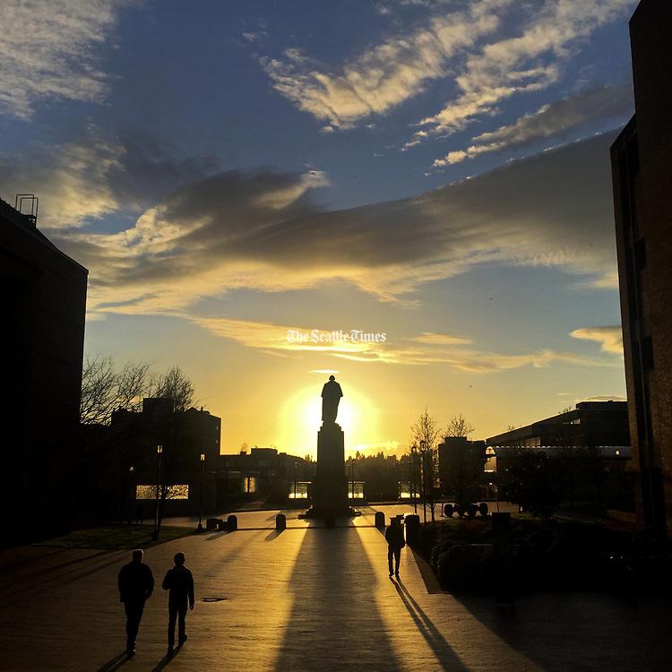 A sunset behind the University of Washington's statue of George Washington illuminates a stunning cloud pattern. (Ken Lambert / The Seattle Times)