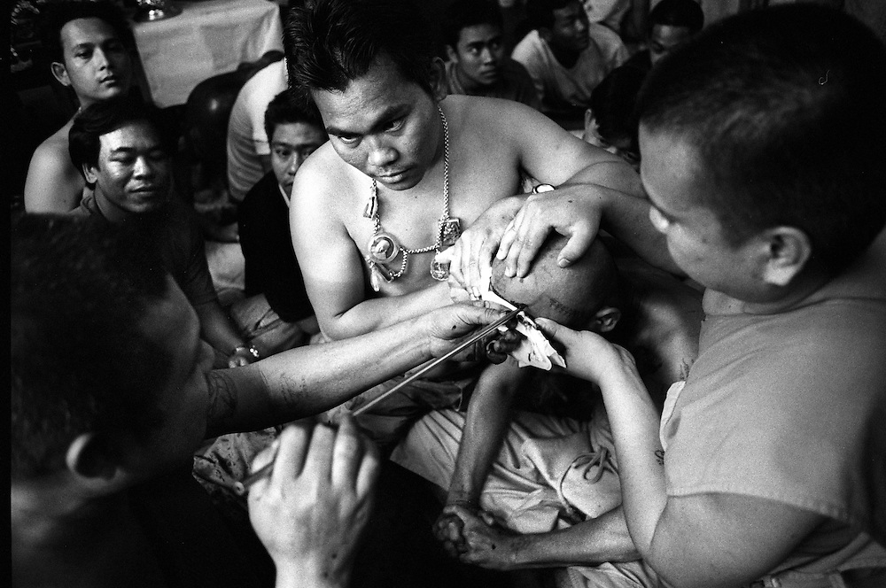 Tattoo Festival at Wat Bang Phra, a Buddhist temple in the town of Nakhorn Chaisri, Thailand - men adorned by Thai Monks with tattoos representing animal spirits often go into a trance claiming they are possessed  by the spirit of the animal. March 2003..©David Dare Parker/AsiaWorks Photography