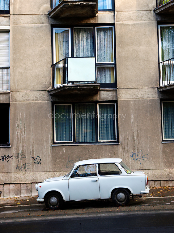 "A classic Trabant car in front of a building block from the communist era. The name Trabant means ""fellow traveler"" (Satellite) in Latin; the name was inspired by Soviet Sputnik. The cars are often referred to as the Trabbi or Trabi, pronounced with a short a. It was the most common vehicle in East Germany, and was also exported to countries both inside and outside the communist bloc. The main selling points were that it had room for four adults and luggage, and was compact, light and durable. Despite its poor performance and smoky two-stroke engine, the car has come to be regarded with affection as a symbol of the more positive sides of former East Germany and of the fall of communism, Budapest, Hungary."