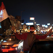 Egyptians cheer and celebrate the resignation of Egyptian President Hosni Mubarak atop cars on a major street in the Mohandiseen district of Cairo February 11, 2011.  (Photo by Scott Nelson)