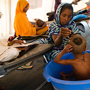 A mother bathing her child at a Médecins Sans Frontières (MSF) stabilisation centre for children suffering from malnutrition at the Mbera refugee camp in southeastern Mauritania on 1 March 2013.