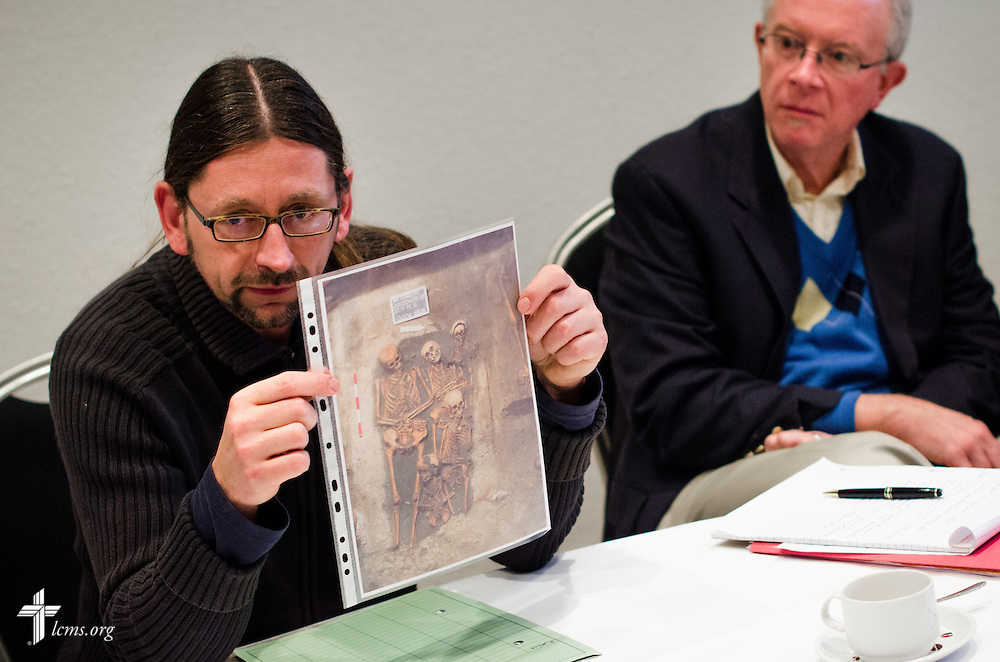 An archeologist presents a photograph depicting a buried family found in the shaft of the Old Latin School  Wednesday, Jan. 29, 2014, in Wittenberg, Germany. LCMS Communications/Erik M. Lunsford