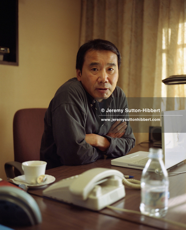 Haruki Murakami, born 1949,  Japanese contemporary fiction author / novelist / essayist, sitting at a desk with his Apple Mac G4 laptop. Photographed in Kagurazaka district of Tokyo, Japan. 14.12.2004 Murakmai is author of noted books such as 'Norwegian Wood', 'A Wild Sheep Chase', 'Underground', 'After the quake' and 'Kafka on the Shore'.