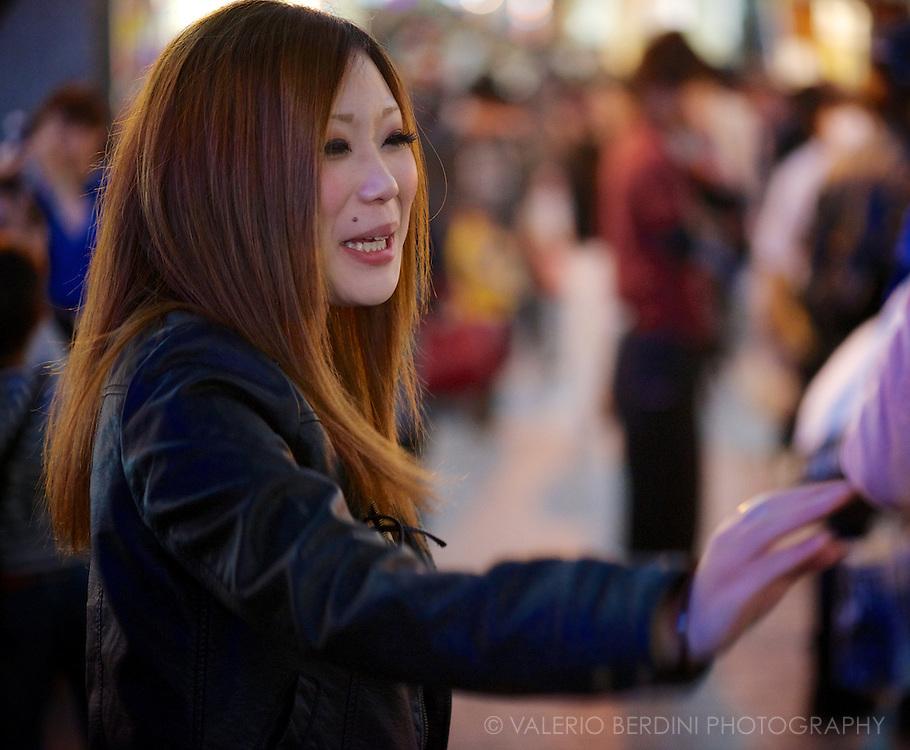 One hostess chasing customers on the nanpa-bashi. Osaka, Japan 2013