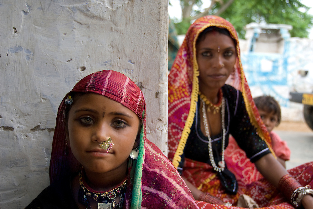 A young Rajasthani girl wearing a typical dress, her mother and younger sister at the back.