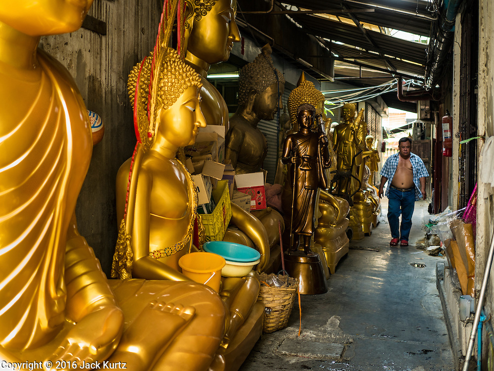 09 MARCH 2016 - BANGKOK, THAILAND: A worker leaves a small workshop that makes statues of the Buddha on Thanon Bamrung Muang in Bangkok. The street is lined with workshops that make statues of the Buddha and revered Thai Buddhist monks. Once located just outside Bangkok's city walls, it's now in the heart of the city.     PHOTO BY JACK KURTZ