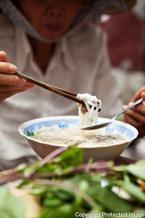 tucking into a bowl of noodles at a ho chi minh city street stall, vietnam