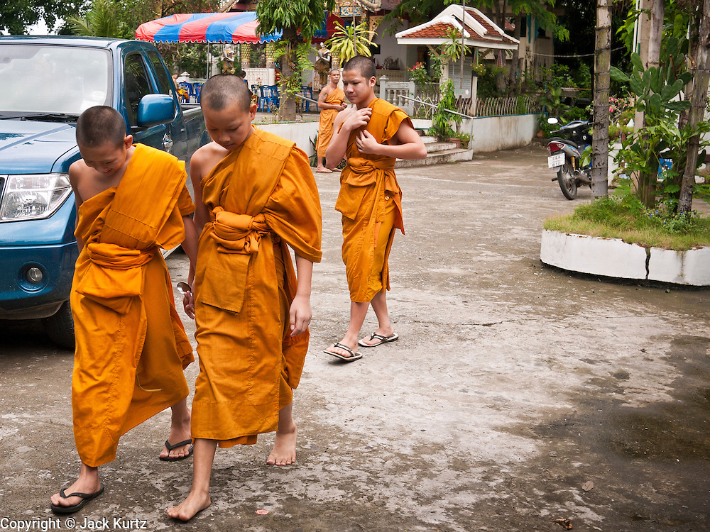 28 JUNE 2011 - CHIANG MAI, THAILAND: Novice monks walk through Wat Phrathat Doi Saket, a large temple complex in Chiang Mai, Thailand. The temple at Doi Saket is said to have been built in the year 1112, but it has been renovated several times since then.  PHOTO BY JACK KURTZ