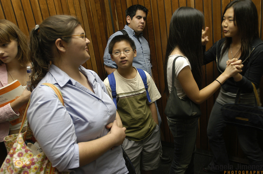 """Young classical music students in the Pre-College Division program at The Juilliard School of music crowd into elevators between sessions of their weekly lessons at the school, located at West 65th Street and Broadway in New York City, on Saturday, September 24, 2005. Violinist Elizabeth """"Libby"""" Fayette of Long Island, New York, 17, second from left, talks with other students in the elevator. Students audition for spots in the prestigious program, in which they can study until they graduate from high school."""