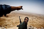 LIBYAN ARAB JAMAHIRIYA, Nalut : A rebel fighter walks near the front line, close to the southwest Libyan village of Gazaia (Top R), as rebels attack forces loyal to Moamer Kadhafi, on July 28, 2011. ALESSIO ROMENZI