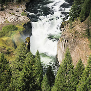 Lower Mesa Falls plunges 65 feet along Henrys Fork (also known as North Fork, a tributary of the Snake River) in Caribou-Targhee National Forest near Ashton in southeastern Idaho, USA. The falls flow over Mesa Falls Tuff, which formed 1.3 million years ago. A cycle of rhyolitic volcanism from the Henrys Fork caldera depositing a thick layer of rock and ash which compressed and hardened over time. Between 200,000 and 600,000 years ago, the river eroded a wide canyon which was subsequently partly filled with basalt lava flows. The Henrys Fork of the Snake River carved a channel through the basalt to create todays inner canyon.