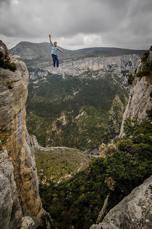 Daredevil Mich Kemeter crossing a highline (tight rope walking) in free solo (no safety rope) 300m above the ground in Verdon Canyon, South of France.