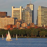 Boston skyline photography showing iconic Boston skyscrapers. The foreground is made off building reflections and Charles River sailboats sailing along. <br />
