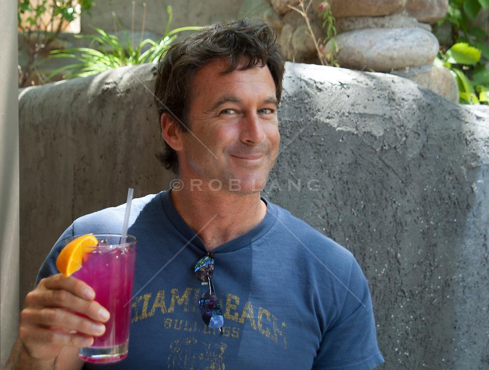 good looking man enjoying a pink drink outdoors