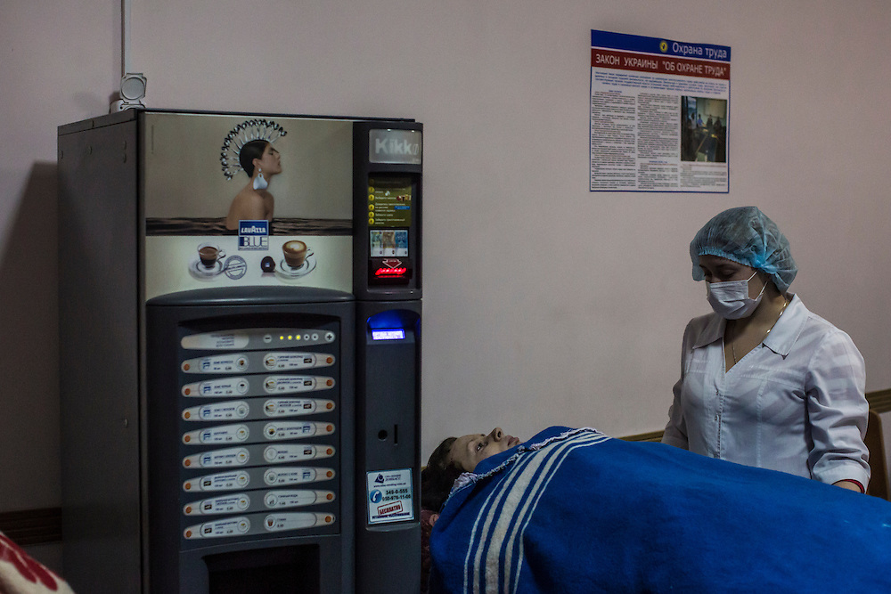 DONETSK, UKRAINE - JANUARY 26, 2015: A woman who was wounded by a rocket attack is tended to by a nurse in Vishnevskogo Hospital in Donetsk, Ukraine. A rocket hit her home, injuring her nine-month-old daughter and killing her mother. CREDIT: Brendan Hoffman for The New York Times